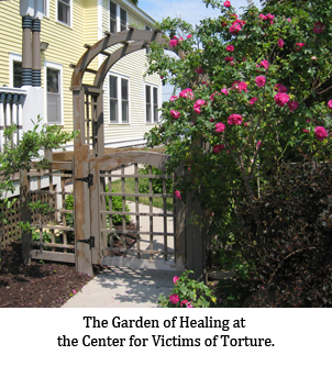 The Garden of Healing at the Center for Victims of Torture. A wooden gate welcomes visitors with a profusion of bright flowers.