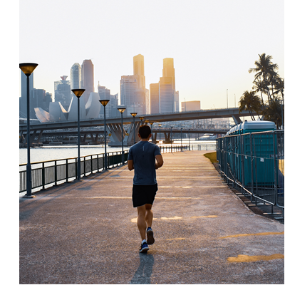Photograph of a man jogging down an empty sidewalk with a city in the background. Photo by Gervyn Louis on Unsplash