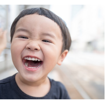 Photo of child laughing. Photo by kazuend on Unsplash
