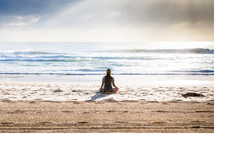 Photo of woman meditating sitting on a sandy beach on a sunny day. Photo by Simon Rae on Unsplash