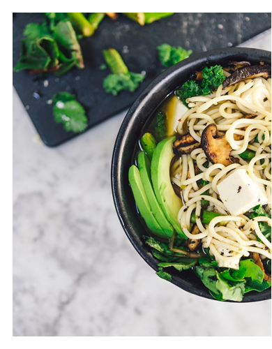 Photograph of bowl of noodles with avocados, mushrooms, broccoli and tofu. Photo by The Creative Exchange on Unsplash